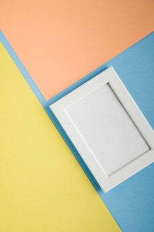Flat lay white frame with light colorful background