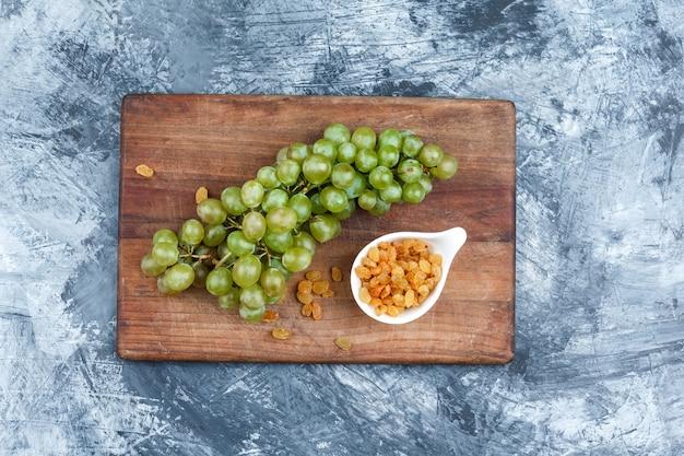 Плоские лежал белый виноград, изюм на разделочной доске на темно-синем мраморном фоне. горизонтальный