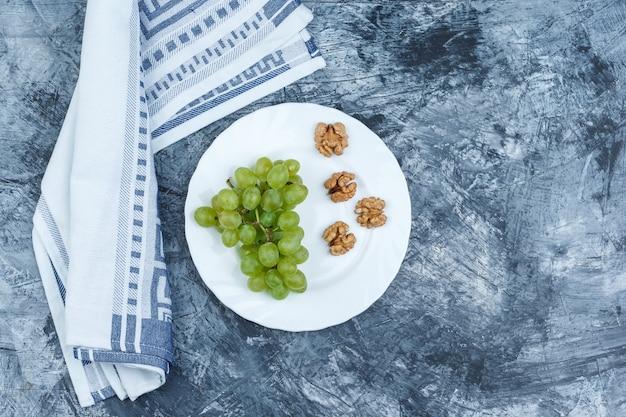平らに置いた白いブドウ、ダークブルーの大理石の背景にキッチンタオルと白いプレートのクルミ。水平
