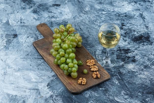 紺碧の大理石の背景にワインのグラスとまな板のフラットレイ白ブドウ、クルミ。水平