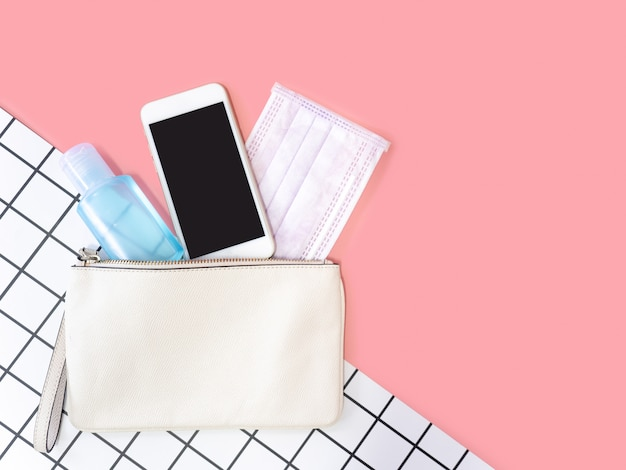 Flat lay of white leather woman bag with smartphone, surgical mask and alcohol gel sanitizer on pink background, top view with copy space for text.