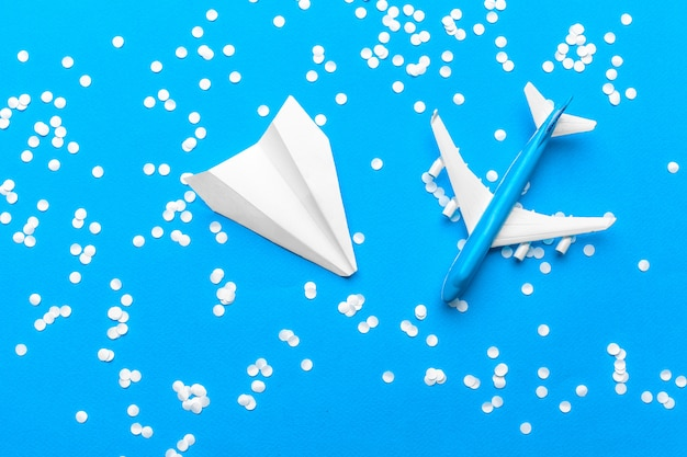 Flat lay of white paper plane and blank paper on pastel blue color