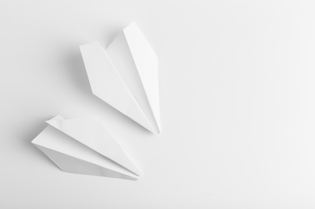 Flat lay of white paper plane on white color background