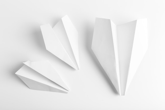 Flat lay of white paper plane on white color