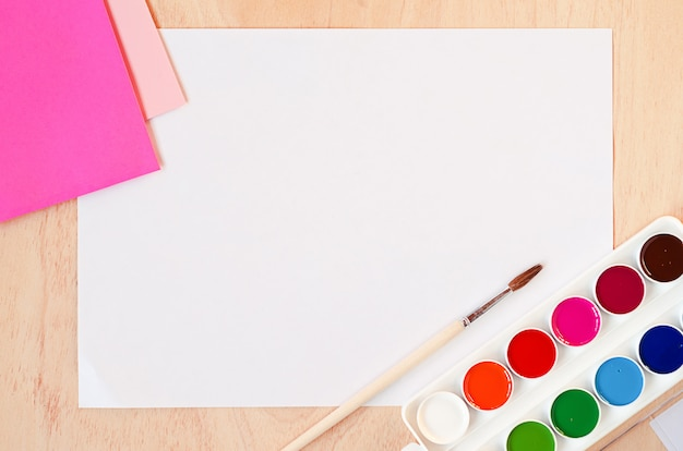 Flat lay white sheet of paper, new watercolor paints and a set of trendy pink colors on the palette,.