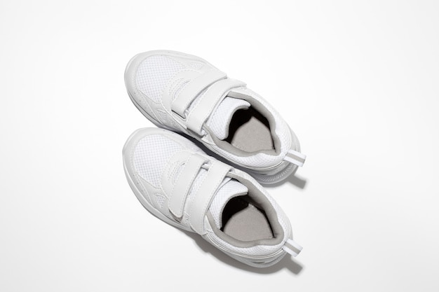 Flat lay white sneakers with velcro fasteners for pregnant women or people with disabilities isolate...