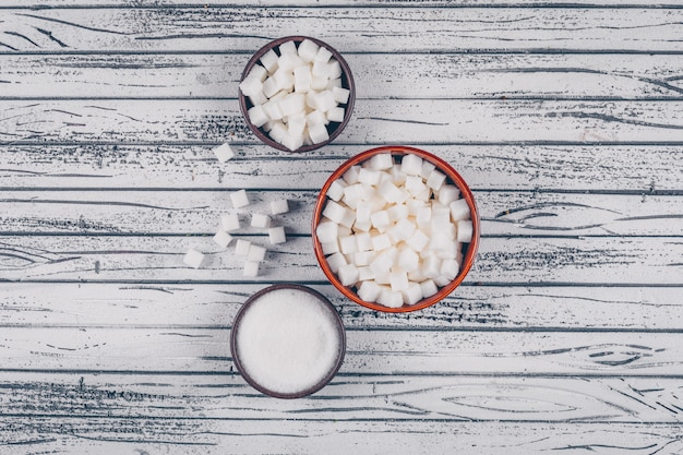 Flat lay white sugar in bowls on white wooden table. horizontal