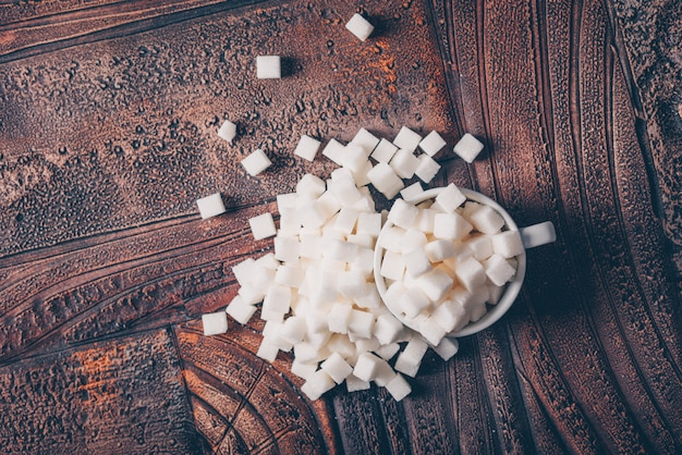 Flat lay white sugar cubes in cup on dark wooden table. horizontal