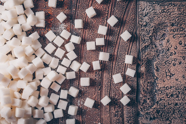 Flat lay white sugar cubes on dark wooden table. horizontal