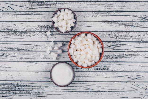 Плоские кладут белый сахар в миски на белый деревянный стол. горизонтальный