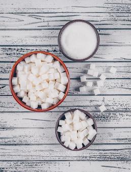 Плоские кладут белый сахар в миски на белый деревянный стол. вертикальный