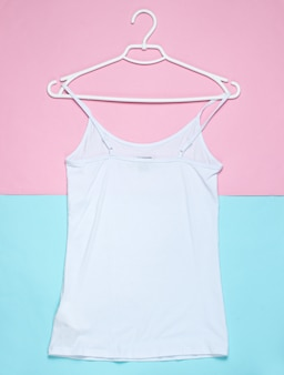 Flat lay of white t-shirt with hanger on pastel background.
