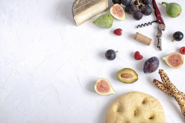 Flat lay  wine appetizer fig prosciutto grape plum cheese focaccia grissini