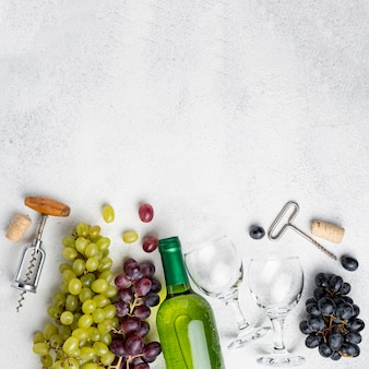 Flat lay wine bottles of grapes with corkscrew