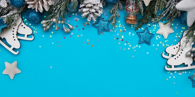 Flat lay winter header: spruce twigs in the snow with cristmas decoration in blue, silver, white colors