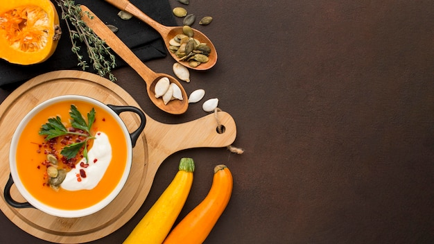 Flat lay of winter squash soup in bowl on chopping board with copy space
