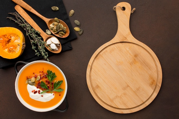 Flat lay of winter squash soup in bowl with chopping board and spoons