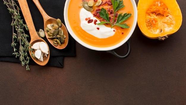 Lay piatto di zuppa di zucca invernale nella ciotola con copia spazio e cucchiai