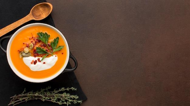 Lay piatto di zuppa di zucca invernale nella ciotola con prezzemolo e copia spazio
