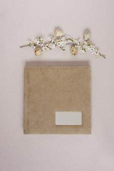 ベージュのフォトアルバムまたは碑文用の金属フレームのある本、白い花とベージュの背景にイースターエッグのある春の枝を備えたフラットレイ。上面図、コピースペース