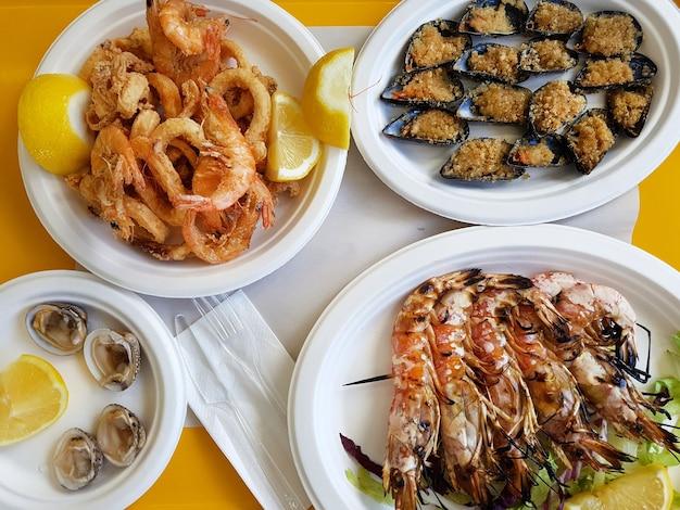 オレンジ色のテーブルの上のプラスチックプレートに調理されたシーフード製品の品揃えでフラットレイ。殻付きのムール貝、エビ、イカのレモン添えの上面図。テイクアウト食品、テイクアウト配達