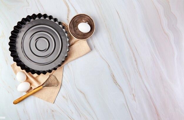 大理石の上にタルト、クッキー、生地、ペストリー用の調理器具と調理材料を使ったフラットレイ。