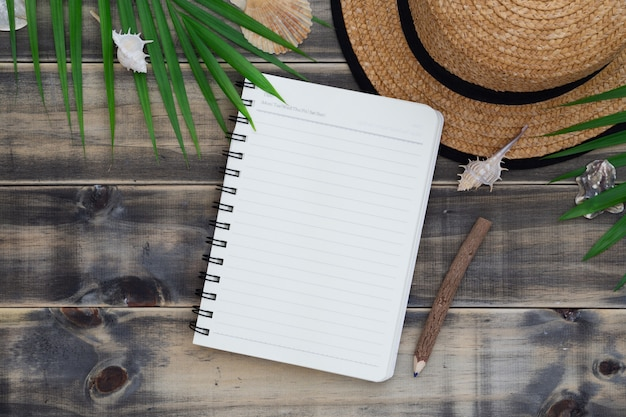 Flat lay with beach hat, sea shells, palm leaves and blank notebook and pencil.