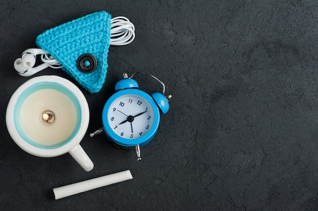 Flat lay with blue alarm clock, chalk background