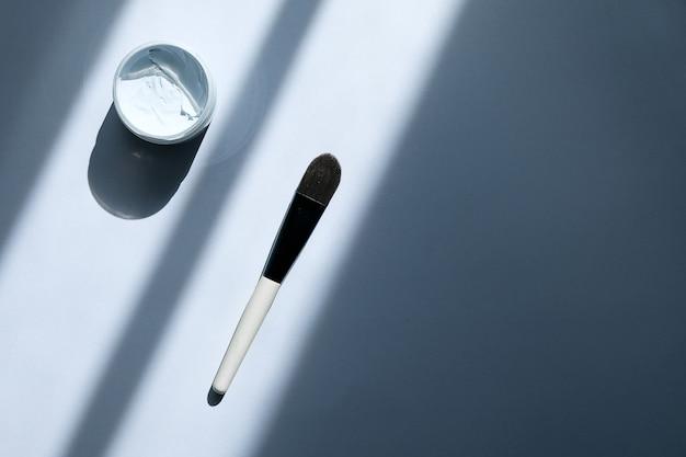 平らな瓶の中の青い粘土facelマスクを置きます。顔用化粧品と美しさの背景