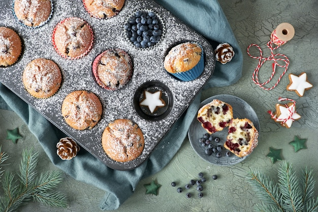 Flat lay with blueberry muffins in a baking tray with christmas decorations