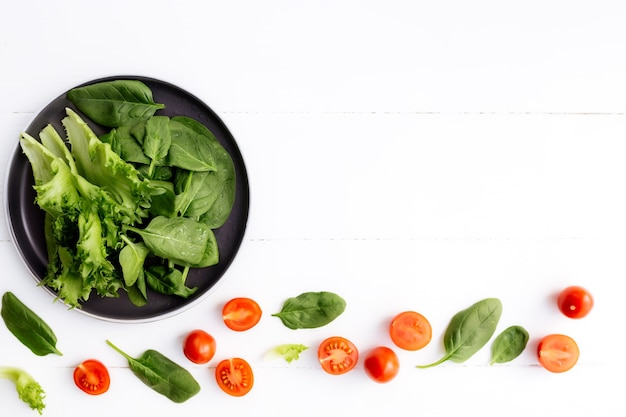 Flat lay with bowl of fresh green salad leaves, lettuce, spinach and red cherry tomatoes cups and halves on a white background