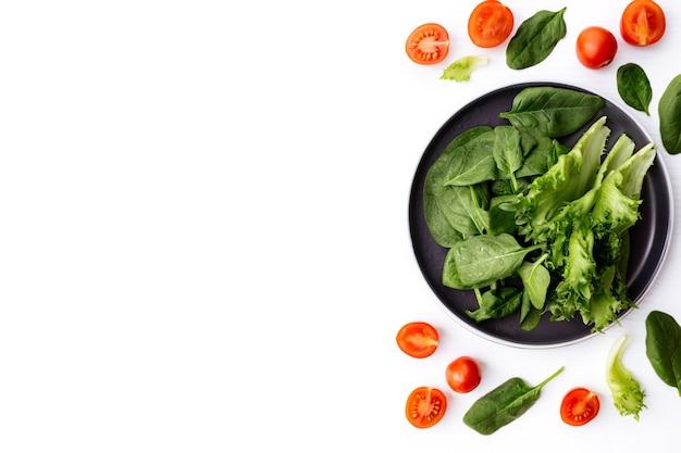 Плоский лежал с миской свежих зеленых листьев салата, салата, шпината и красных чашек и половинок помидоров черри. концепция здорового вегетарианского питания.