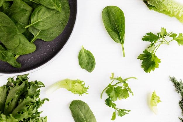 Плоский лежал с миской свежих зеленых салатов, листьев шпината и салата, романа и петрушки, базилика на белом фоне. концепция вегетарианской еды