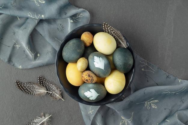 Плоская кладка с миской естественно окрашенных пасхальных яиц на сером столе.