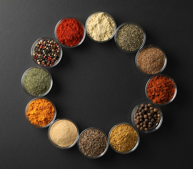 Flat lay with bowls of spices on black background, space for text