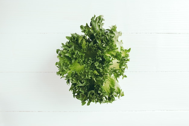Плоский лежал с веткой свежего зеленого салата, листья салата на белом фоне. концепция вегетарианской еды
