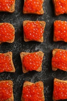 lay piatto con fette di pane con caviale su sfondo nero smokey