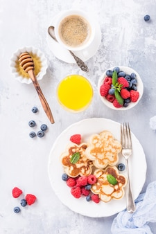Flat lay with breakfast with scotch pancakes in flower form, berries and honey on light wooden table. healthy food concept.