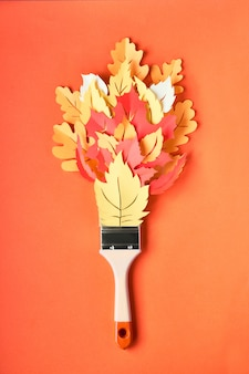 Flat lay with brush loaded with paint made from decorative autumn leaves on orange paper