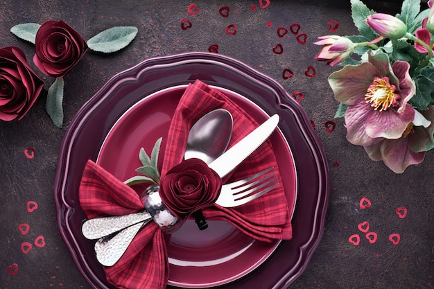 Flat lay with burgindy plates and crockery decorated with roses and anemones, christmas or valentine dinner setup