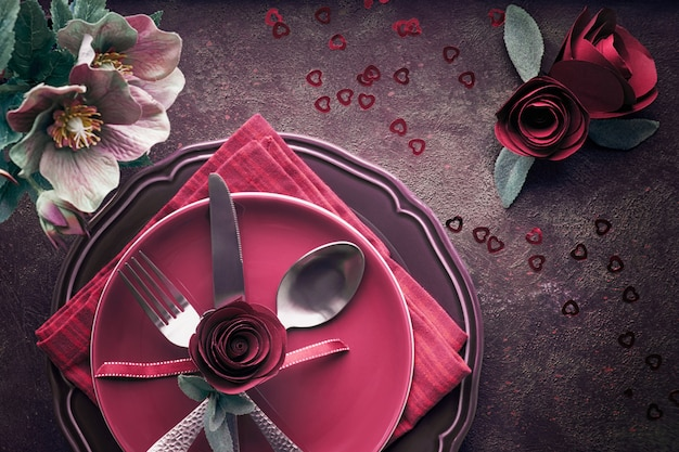 Flat lay with burgindy plates and crockery decorated with roses and anemones,