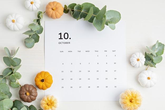 가을 테이블 장식이 있는 10월 달력이 있는 평평한 위치. 수제 호박으로 가을 휴가를 위한 꽃 인테리어 장식. flatlay, 평면도