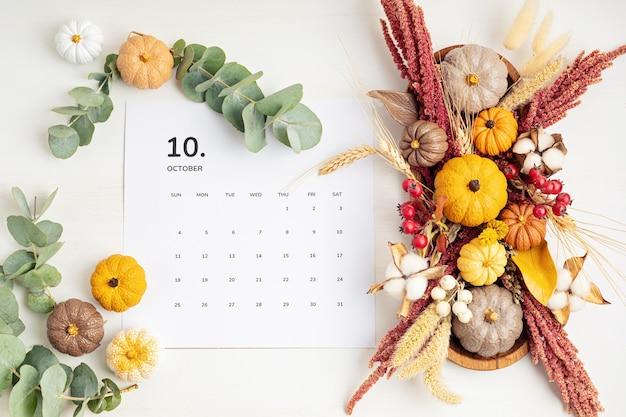 가을 테이블 장식이 있는 10월 달력이 있는 플랫 레이 수제 호박으로 가을 휴가를 위한 꽃 인테리어 장식flatlay, 위쪽 전망