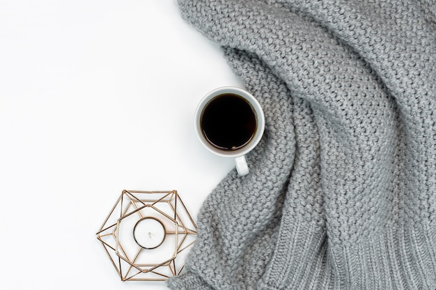 Flat lay with candle, sweater and coffee