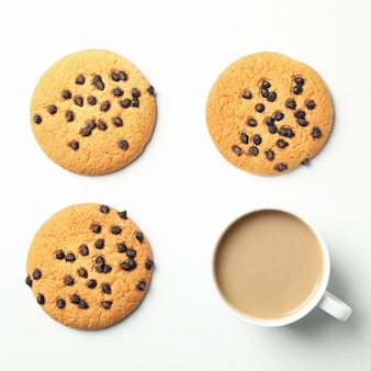 Flat lay with chocolate chip cookies and hot drink on white background