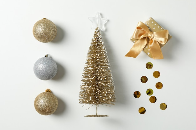 Flat lay with christmas balls, tree, present and confetti on white table