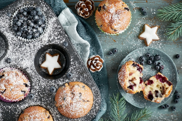 Flat lay with christmas blueberry muffins and xmas decorations on blue
