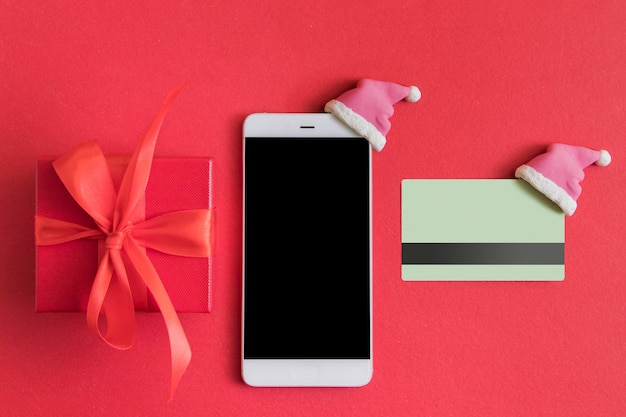 Flat lay with christmas gift box, smartphone and credit card with santa hat on red