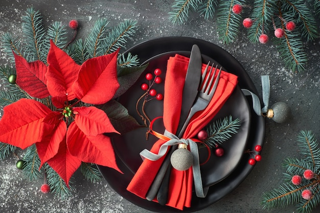 Flat lay with christmas table setting in green and red with crockery, plates and xmas decorations