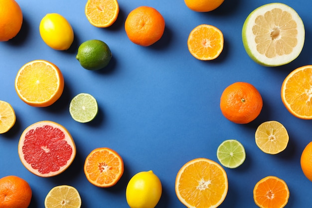 Flat lay with citrus fruits on blue background, space for text